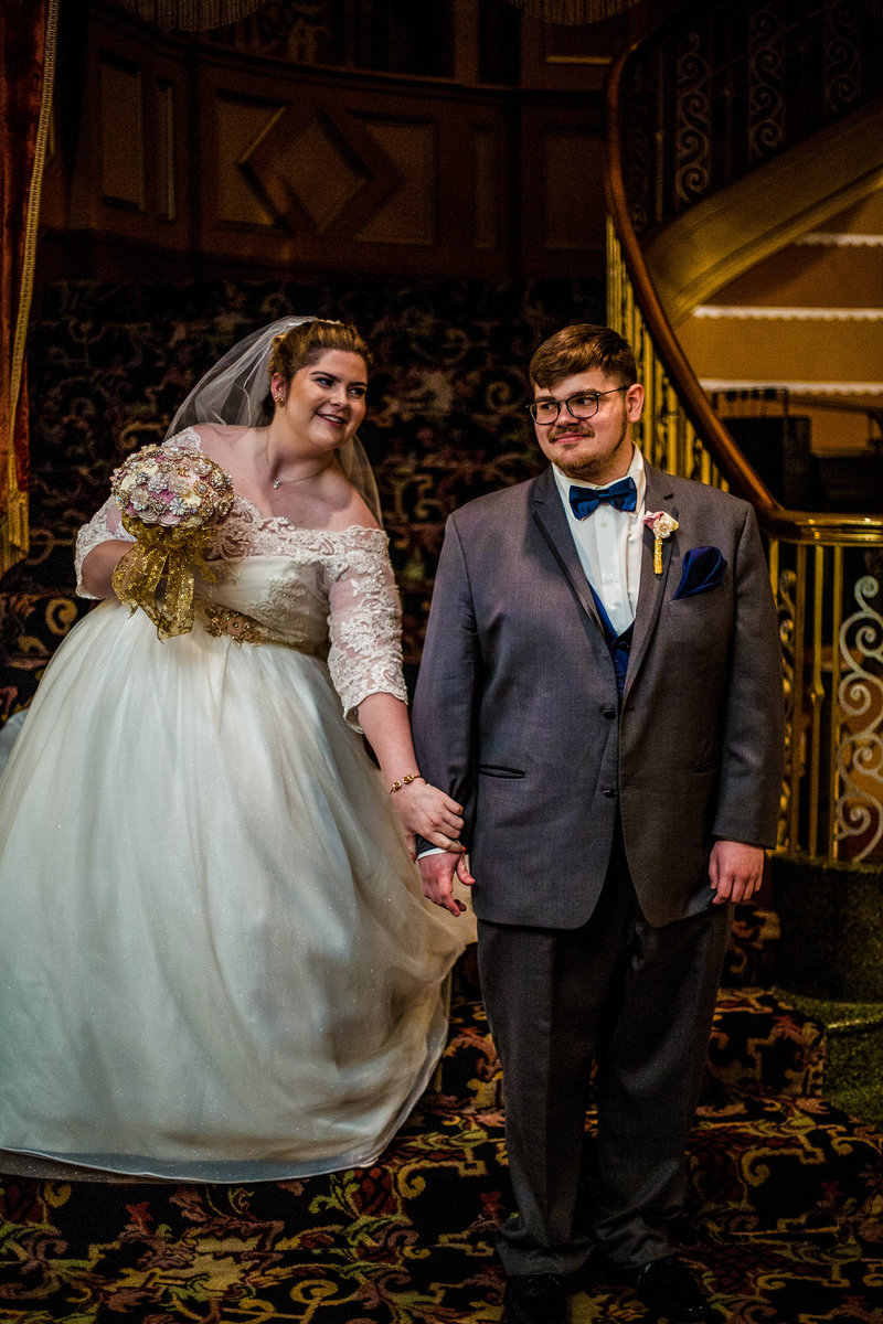 Bride reaching for groom's hand before their first look at the Warner Theatre