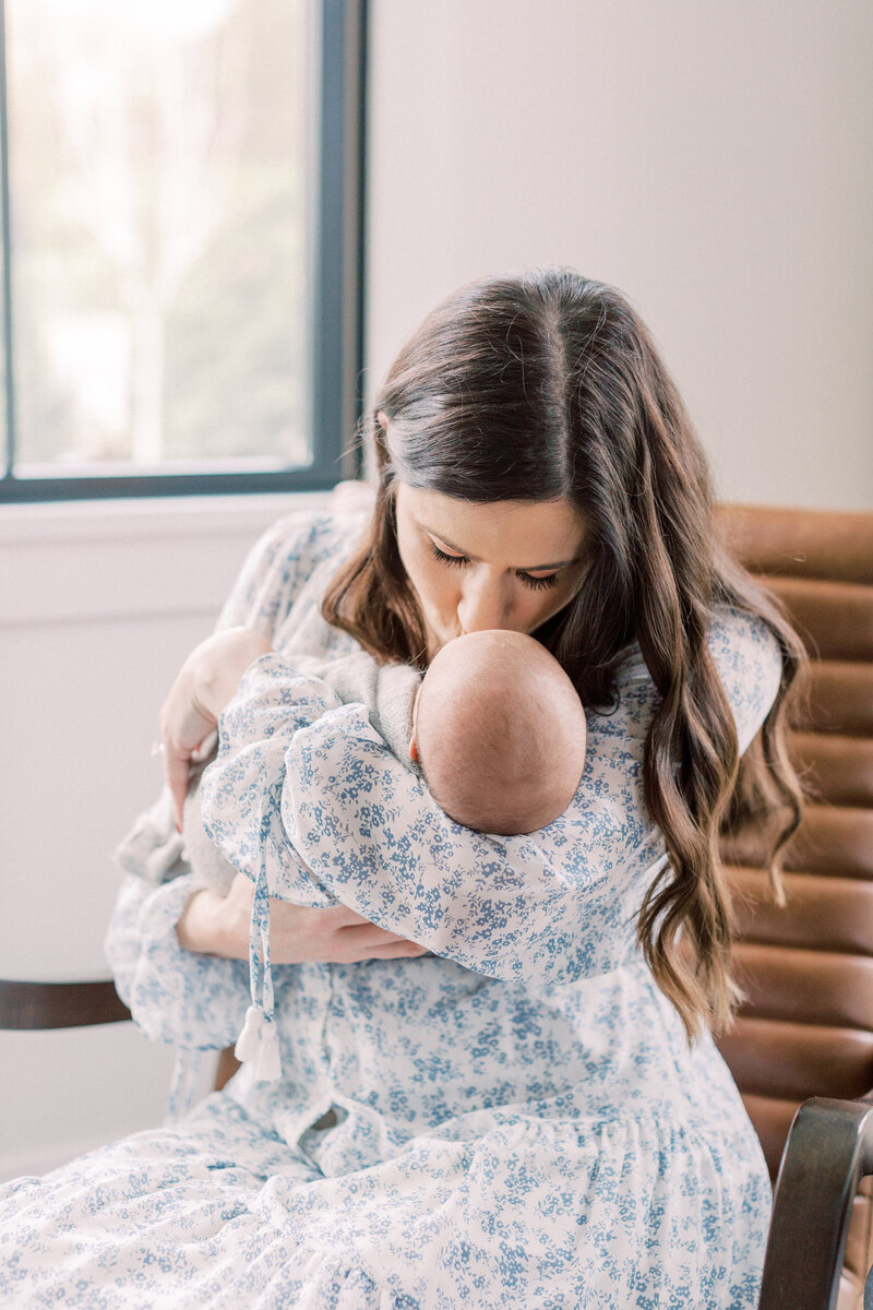 Mother kissing her baby's head during Arlington newborn session