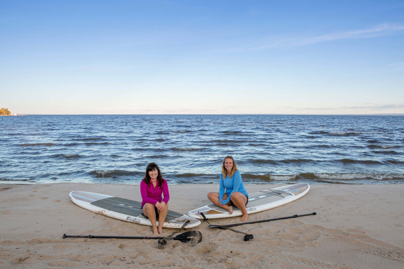 2 women sit on their paddle boards on the  beach