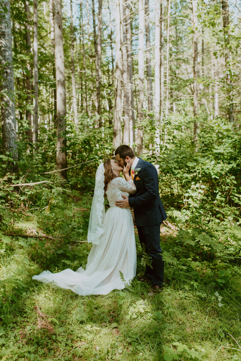 husband and wife kissing in the woods