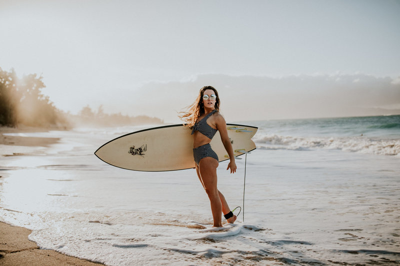 girl at the beach with surfboard