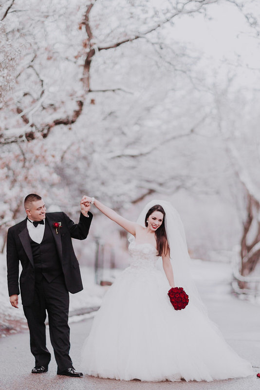 Lake Tahoe wedding photographers a groom dances with his bride in the snow