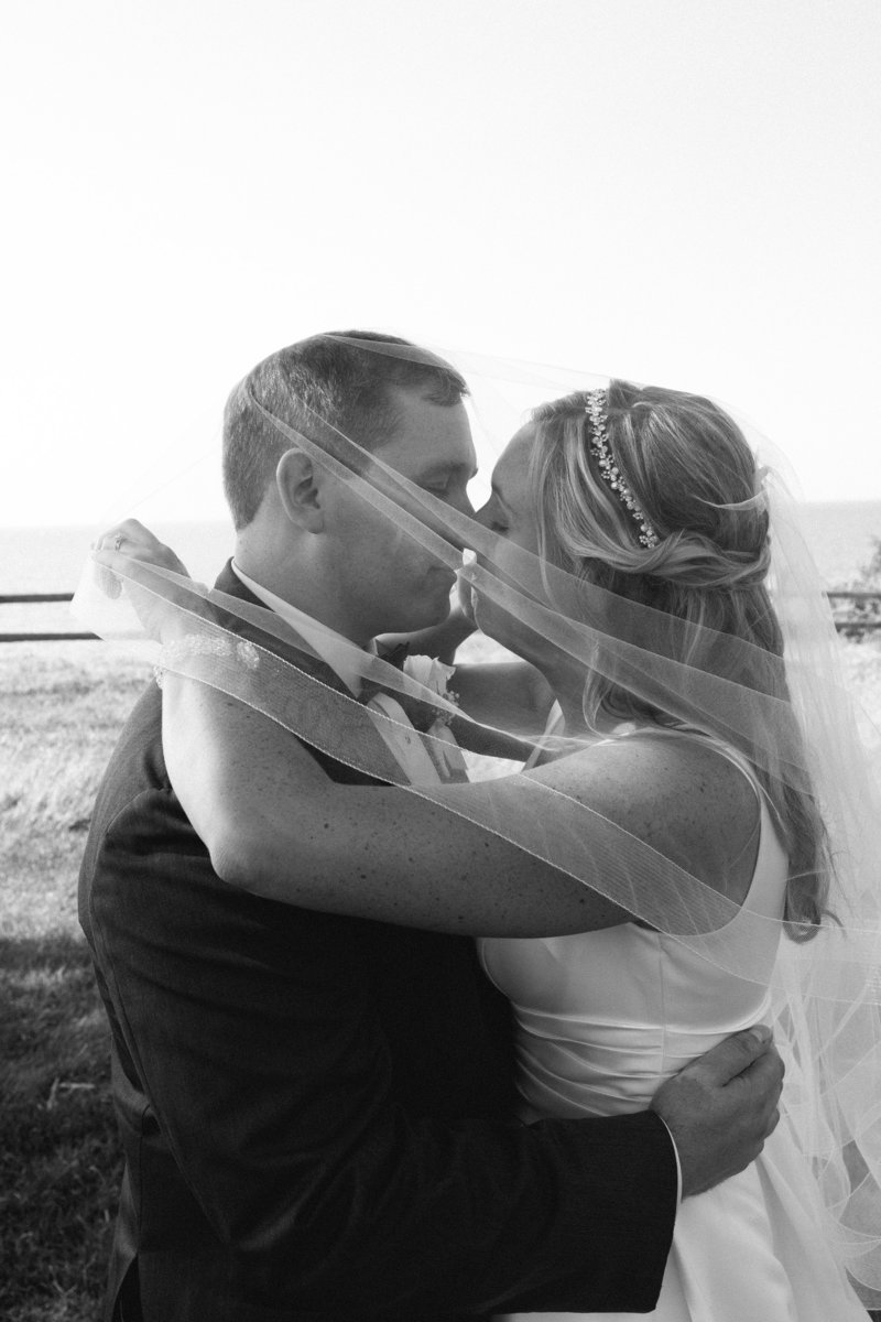 Bride and groom kissing under bride's veil at Lawrence Park golf club