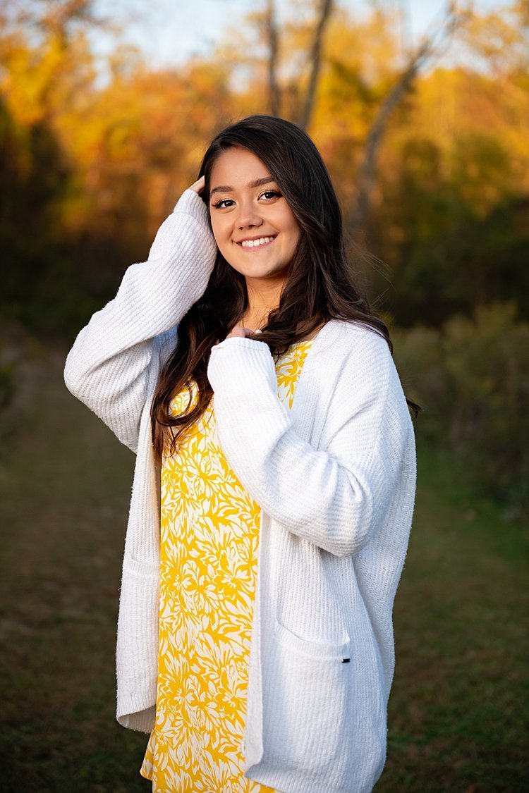 High school senior girl in yellow floral dress with white cardigan standing with hand in her hair along grassy path with fall leaves in background at Round Hill Park in Elizabeth, PA