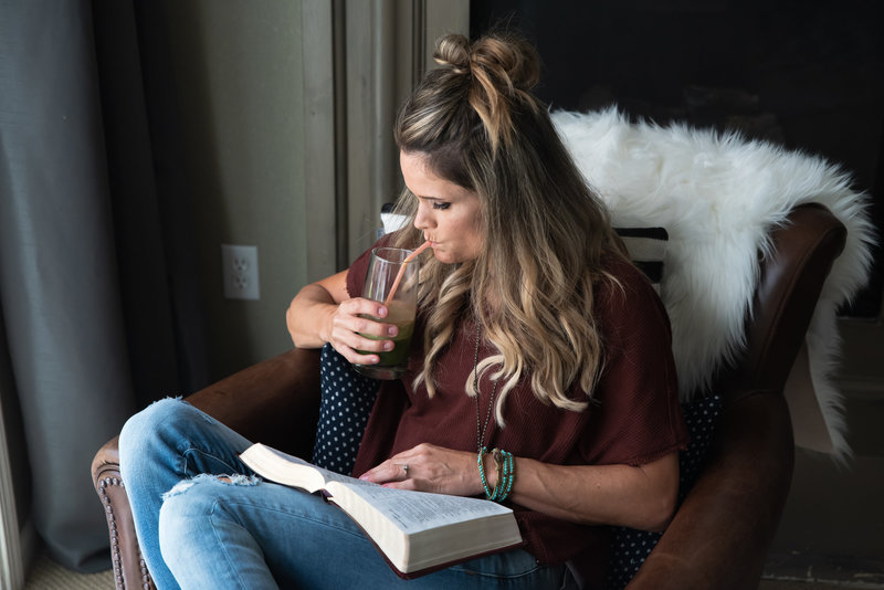personal brand session image; woman drinking smoothie sitting in comfy chair with book
