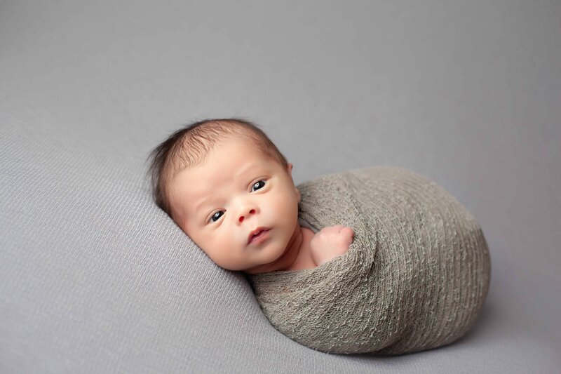 newborn boy in grey wrap and grey backdrop