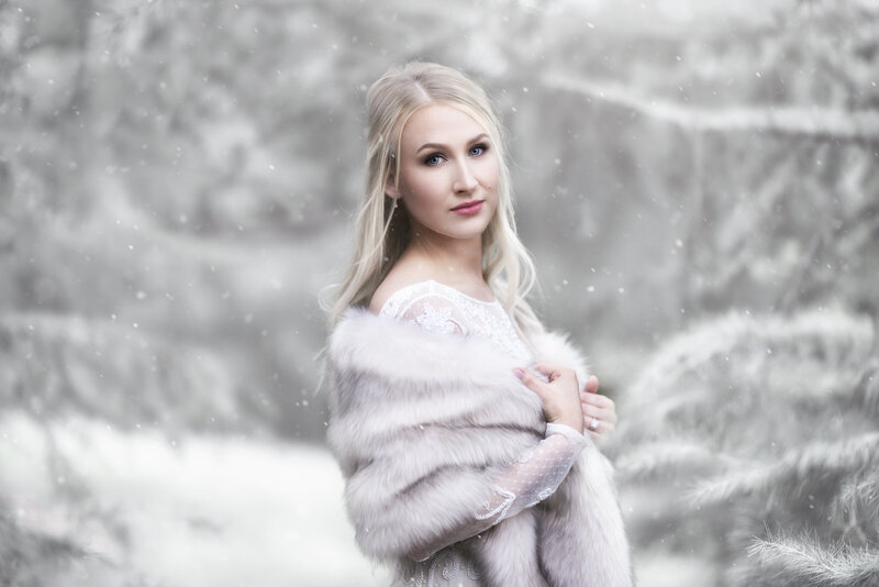 Fine art portrait of Blonde woman with fur and wedding dress in snow at the Dallas Arboretum