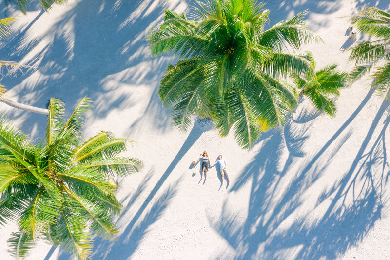 Couple Aeriel Drone view on private beach under palms in Bora Bora