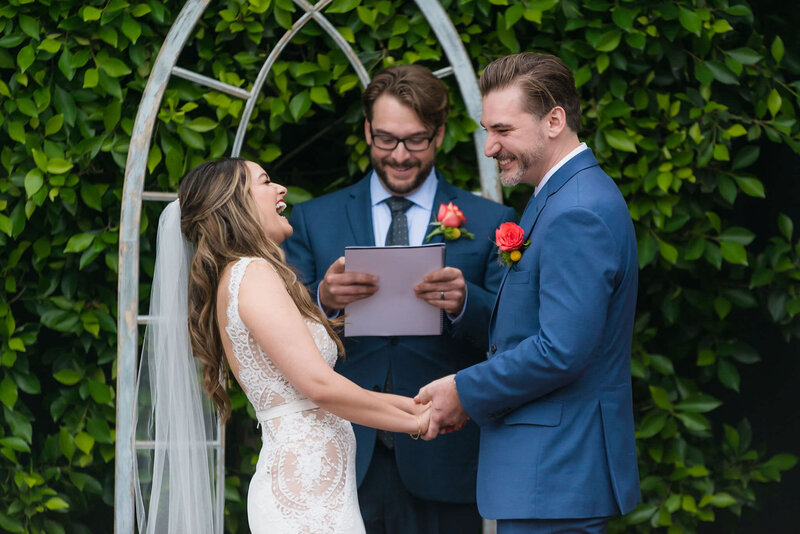 Bride and groom laugh while taking their vows