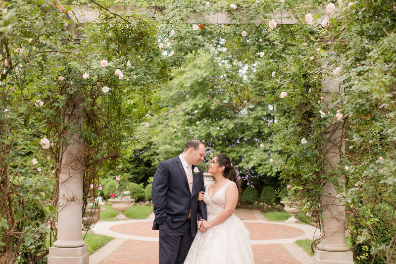 Bride and groom under a rose arch at florentine gardens in New jersey