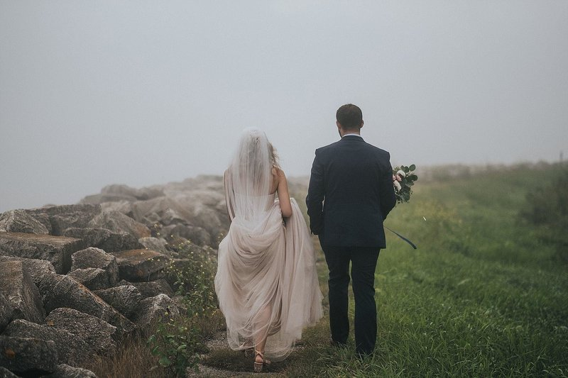 bride and groom walking on foggy day