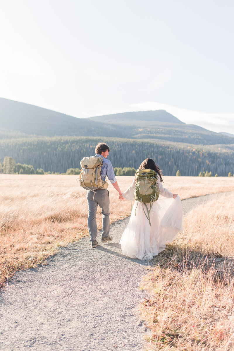 Couple eloping in Colorado wearing hiking backpacks and wedding attire mountains in background | Shot by Houston Texas elopement photographer Samantha Schaub