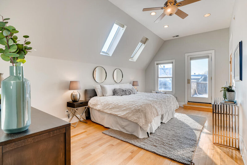 Superior master bedroom after staging light grey upholstered headboard white bedding matching round chrome mirror dark wood and chrome nightstands and chrome console table with a light grey rug underneathe