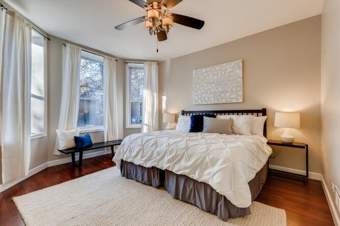 Medill Master Bedroom with black wood headboard white bedding white rug and black wood bench adjacent