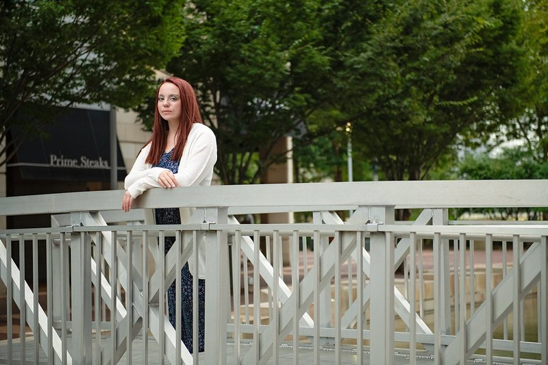 High school senior girl in blue floral jumpsuit with white cardigan leaning on railing of metal walkway in Pittsburgh, PA