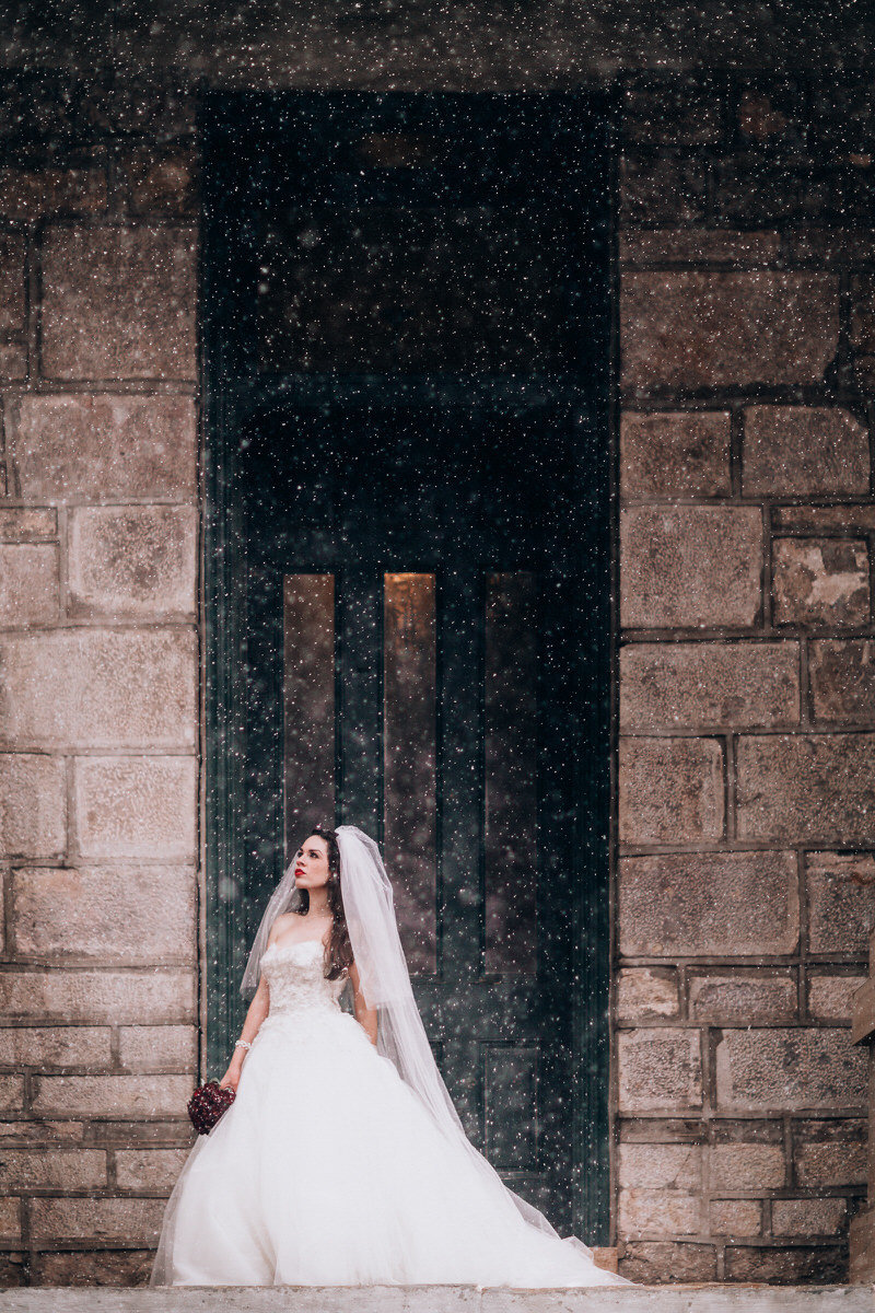 tahoe wedding photographers bride poses in snow in doorway