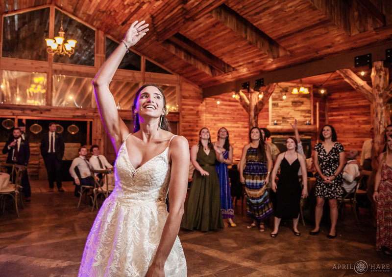 Bouquet Toss at Mountain View Ranch Wedding Reception inside Barn