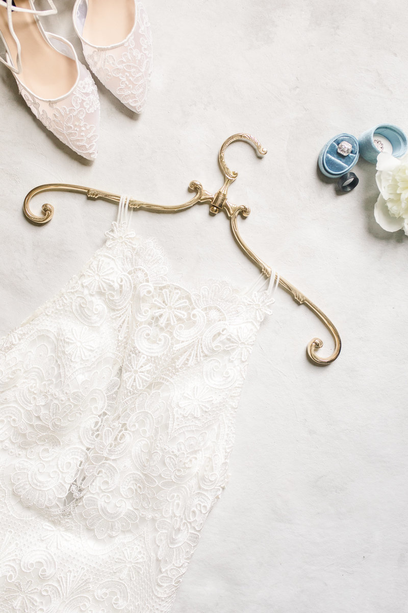 Flat lay of wedding day details of a wedding dress, antique gold hanger, rings and lace wedding shoes