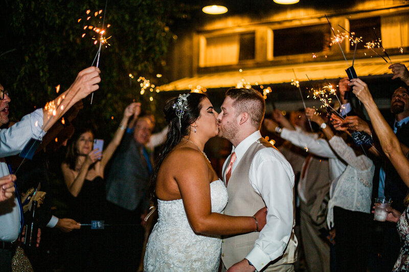 Bride and groom kiss during sparkler exit at Port Farms