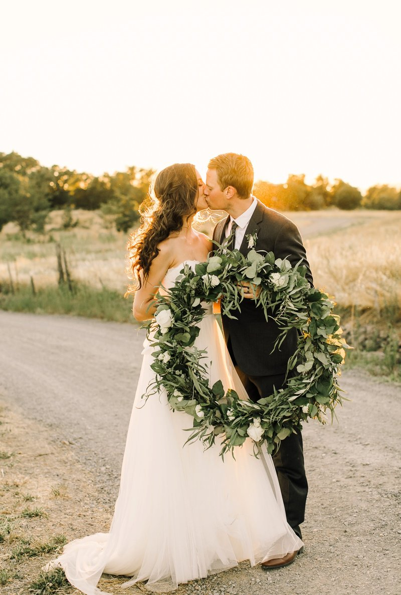 Wedding Photography, couple holding a large wreath of greenery