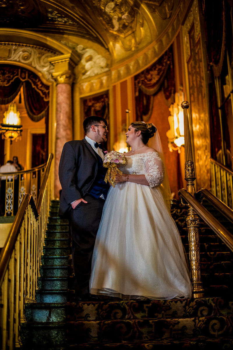 Bride and groom standing on the Grand Staircase at the Warner Theatre