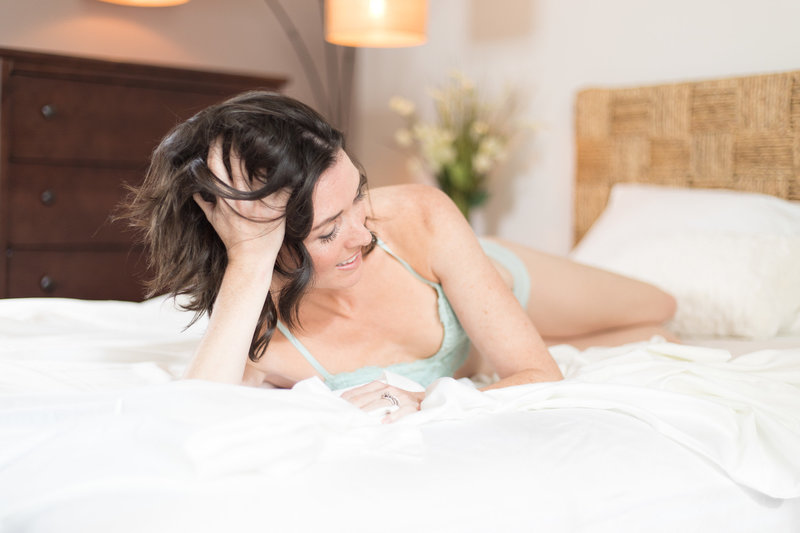 Woman with brown hair lying on her side in a bed with white sheets