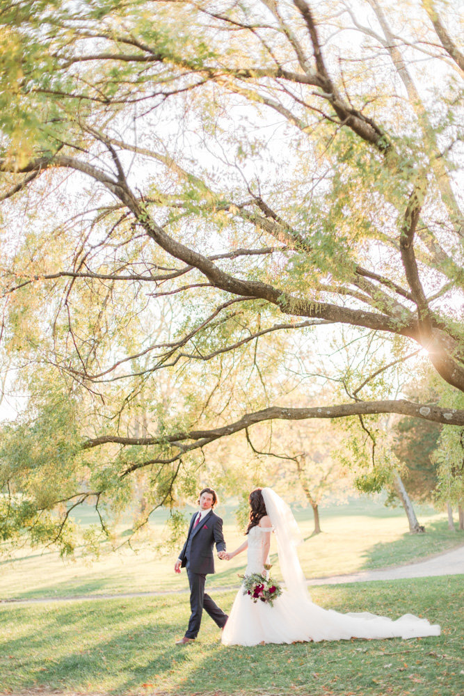 couple walking under the trees at great marsh estate wedding in northern virginia by costola photography