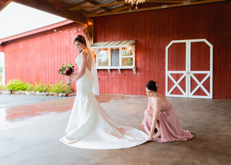 Maid of Honor fixes brides dress / Angel McVay Photography