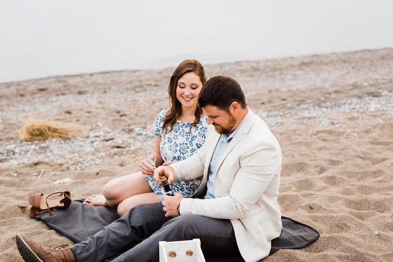 Guy opens a bottle of champagne at point pelee beach during their summer engagement session