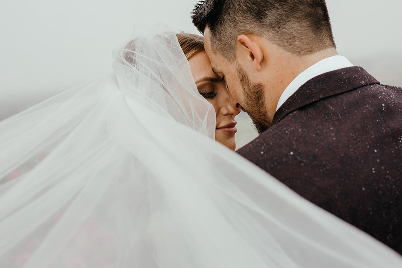 Gorgeous bride in veil embraces her groom at Spokane wedding