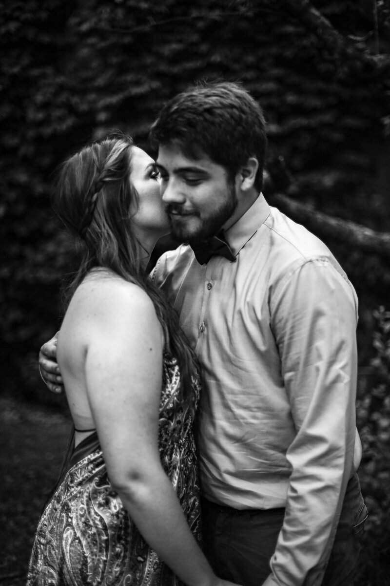 Woman whispers in fiance's ear during engagement photos at Modern Tool Square