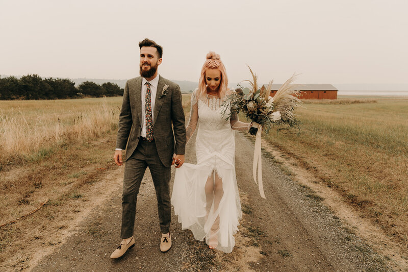 bride and groom holding hands while walking down dirt road