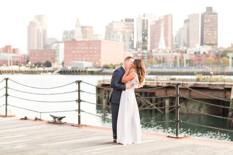 couple kissing in Charlestown Navy Yard with Boston skyline in background