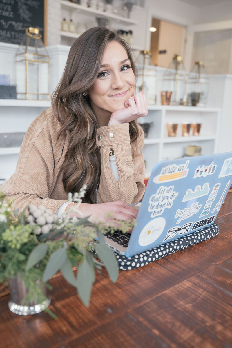 woman smiling with computer in a coffee shop