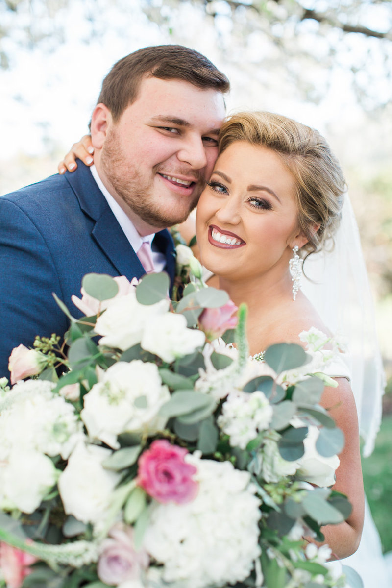 Wedding Photography, bride and groom looking into the camera with large bouquet
