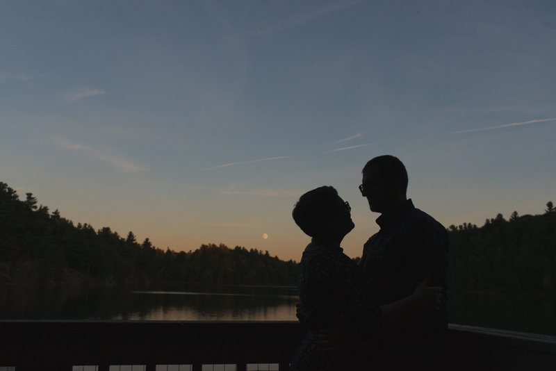 silhouette of engaged couple by the lake at sunset
