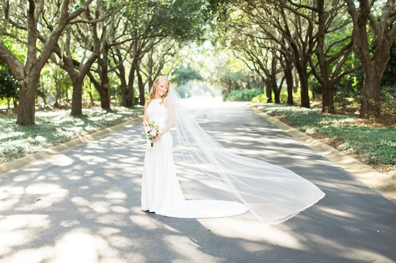 bride posing outside for portraits while veil blows in wind