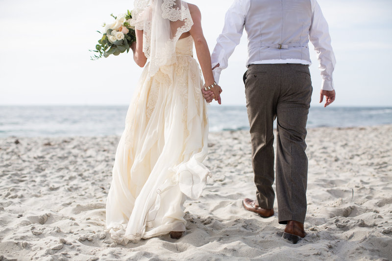 Bride and Groom walking hand in hand on the beach with flowing dress