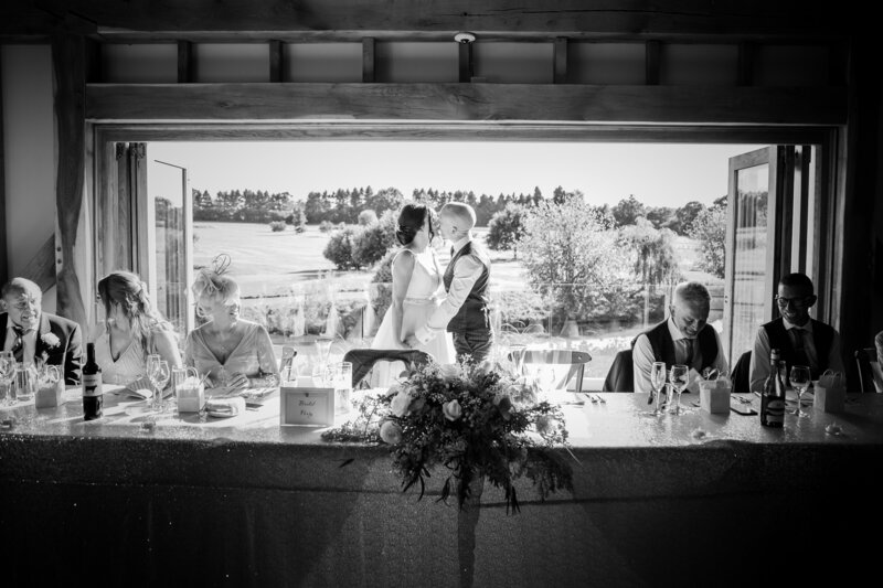 Bride and Groom  kissing  by their top table