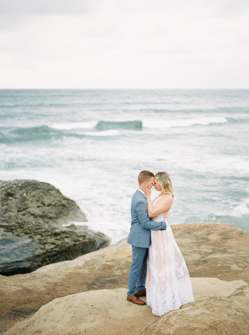 Engagement session at the Sunset Cliffs in San Diego with white dress and light blue suit by Liz Andolina Photography