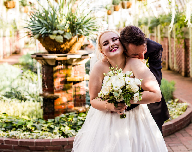 Groom hugs laughing bride at Phipps Conservatory