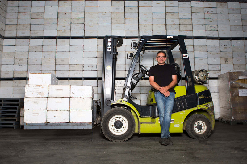 man leans on forklift loaded with beehives