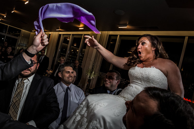 Bride being lifted on chair jewish wedding