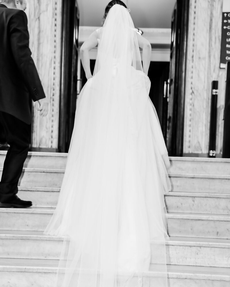 A black and white image showing the back of a bride walking up the stairs to her luxury wedding at a famous hotel.