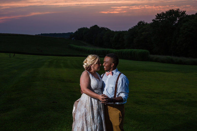Bride and groom smile at each other as the sun sets at Betsy's Barn