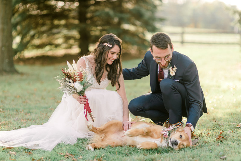 A couple shares a moment with their pup at their wedding