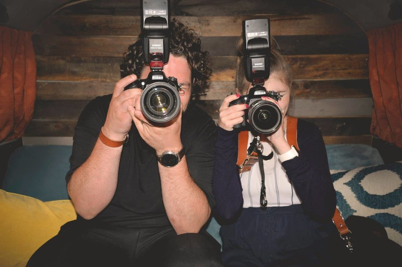 Steven and Stephanie holding cameras looking at the camera