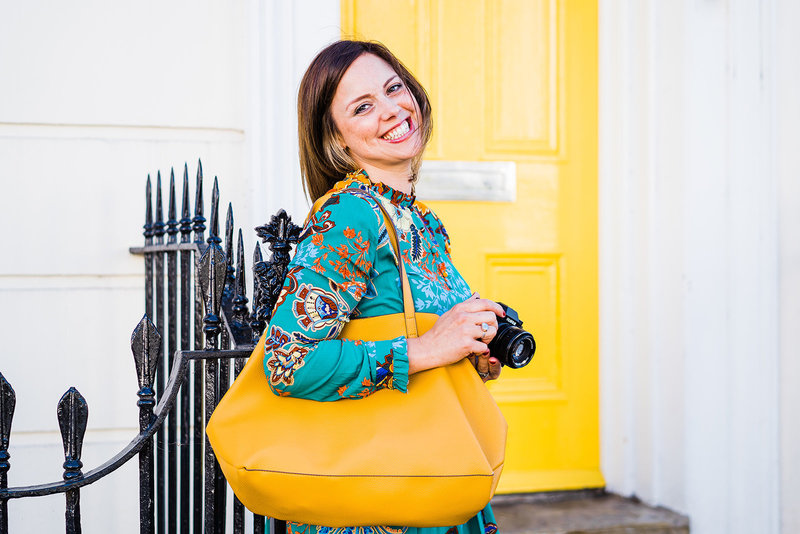 portrait of charlie holding her camera and a yellow bag standing in front of a yellow door in Leamington Spa