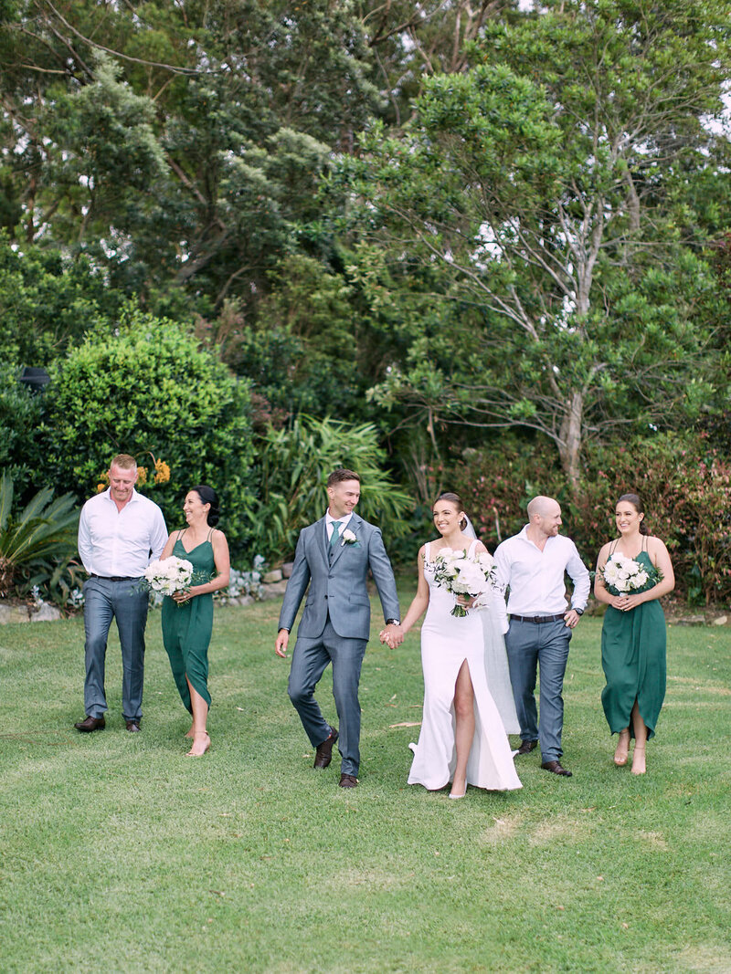 Bridal party walking in gardens laughing