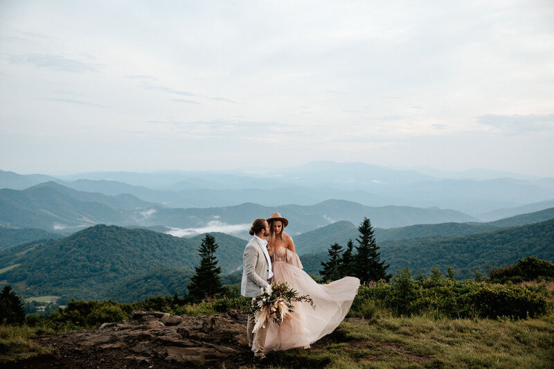 bride and groom standing on a mountain